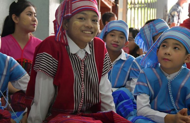Children in traditional clothing for a dance during a visit to a community from Myanmar.