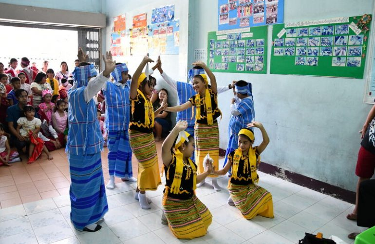 Children perform a traditional dance during a visit to a community from Myanmar.