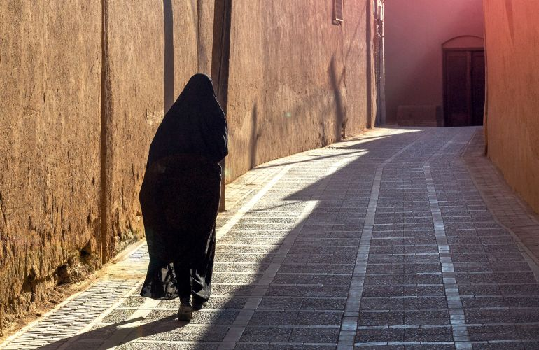 Veiled woman in street